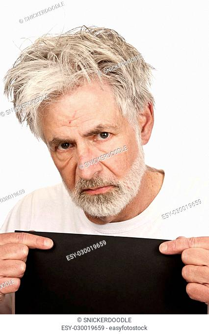 Angry Older Man Being Booked Into Jail holds a blank sign for his information on a white background