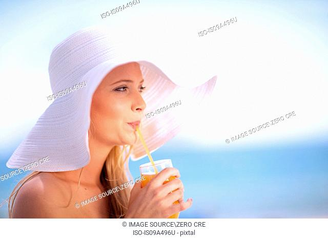 Woman in floppy hat drinking juice