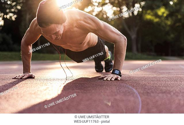 Shirtless man exercing push ups on sport field