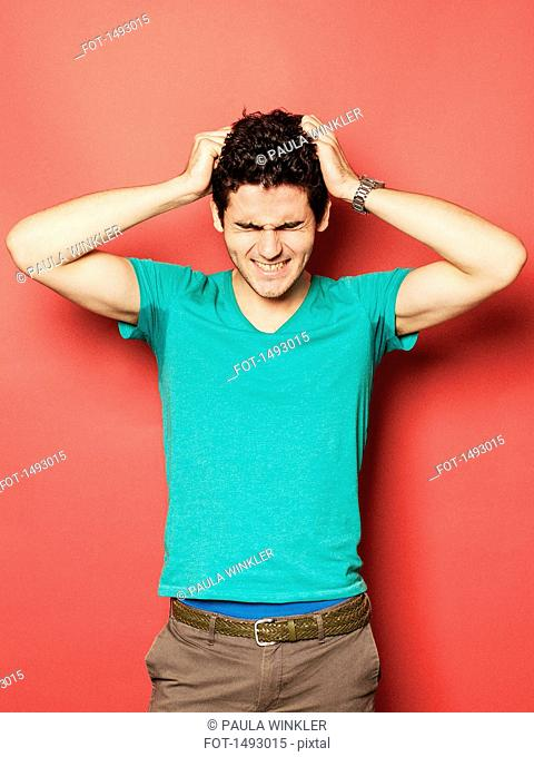 Irritated young man pulling hair against red background