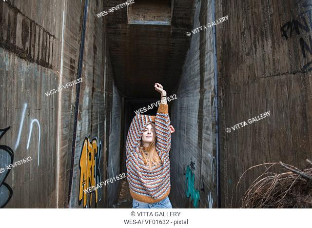 Portrait of young woman raising her arms at graffiti underpass
