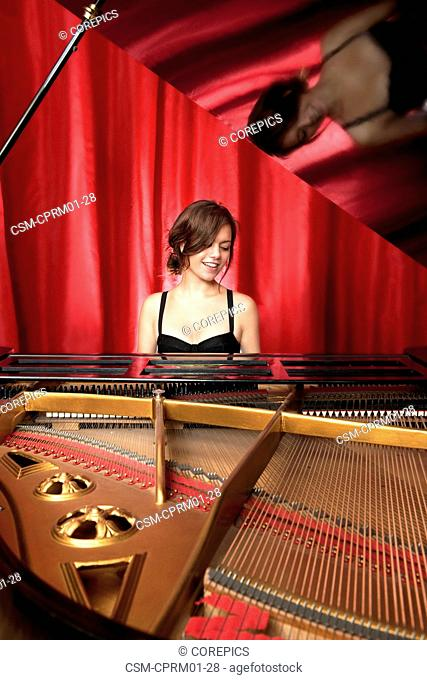 Beautiful pianist smiling whilst playing on a grand piano