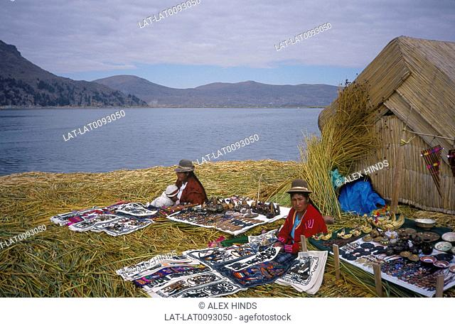 Reed island inhabited by Uros peoples. House. Women seated with goods for sale. Traditional dress