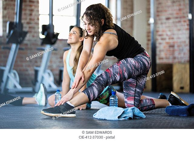 Young woman stretching leg in exercise class