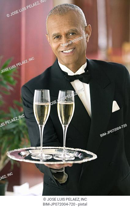 Waiter holding out tray of champagne glasses