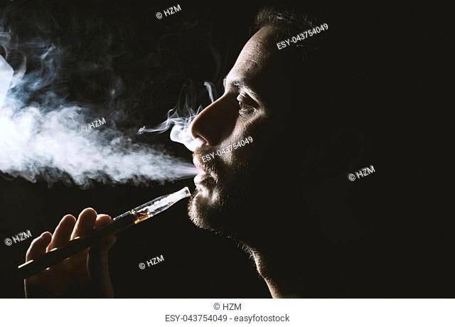 Young man holding and vaping an electronic cigarette, e-cig, ecigarette