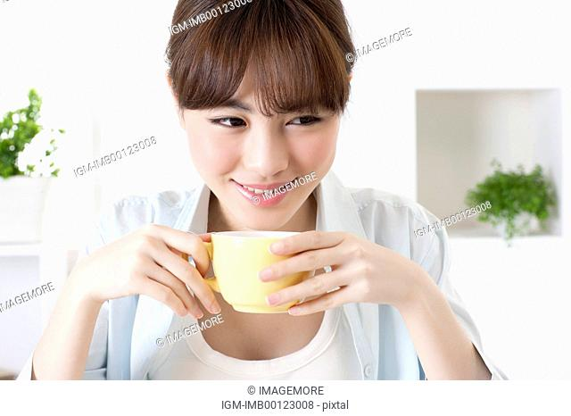 Young woman holding a coffee cup and looking away with smile