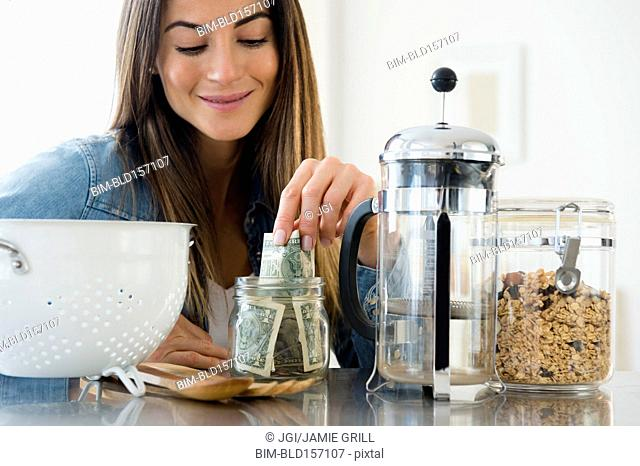 Caucasian woman putting money in jar