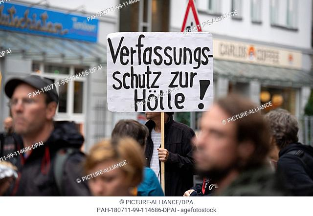 11 July 2018, Germany, Hamburg: A woman carries a sign reading 'Verfassungsschutz zur Hoelle!' (lit. protection of the constitution to hell!) during a...
