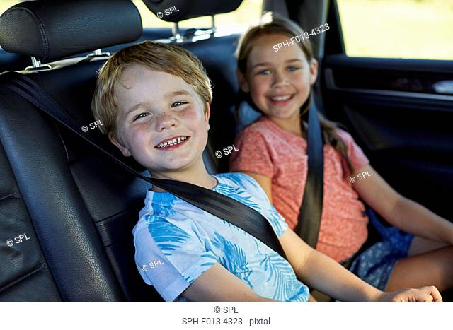 MODEL RELEASED. Brother and sister in the back seat of the car wearing seat belts