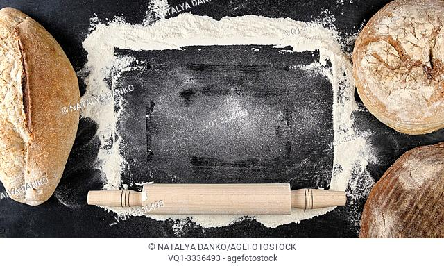 baked various loaves of bread and rolling pin on a black background, empty space in the middle, top view