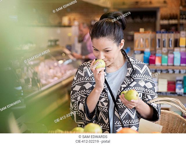 Woman smelling pears in market