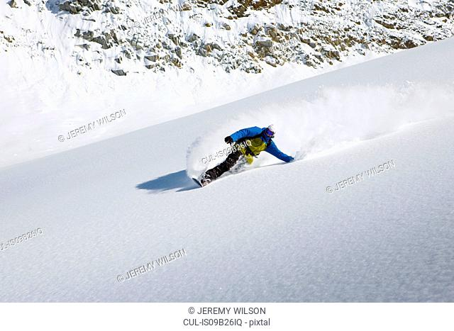 Male snowboarder snowboarding down steep mountain, Trient, Swiss Alps, Switzerland