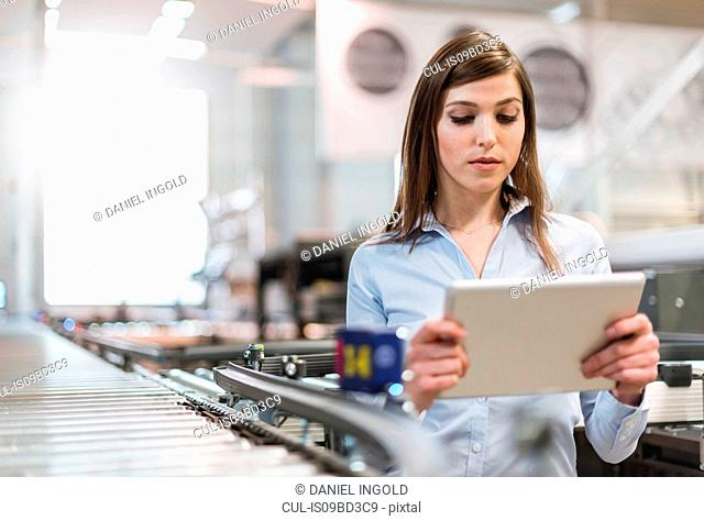 Young woman in factory, beside conveyor belt, looking at digital tablet