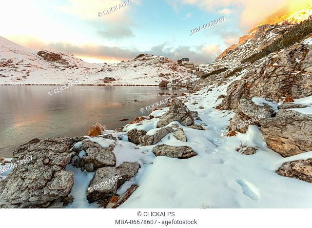 Winter image of Valparola with frozen lake, in the background the refuge of the same name. Dolomites