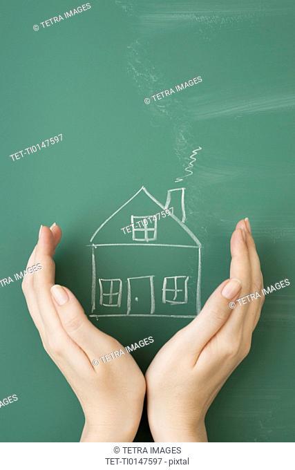 Woman holding hands around house drawn on blackboard