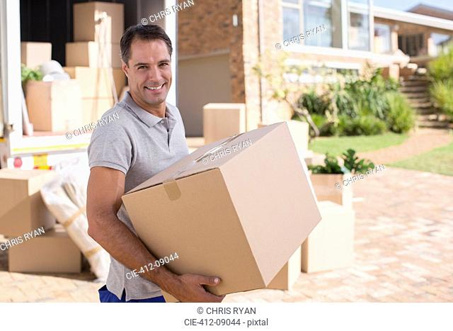 Portrait of man carrying cardboard box from moving van