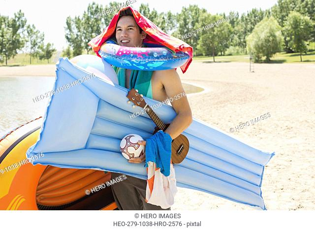 Man carrying inflatable rafts on beach