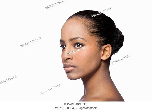 Portrait of serious looking young woman in front of white background