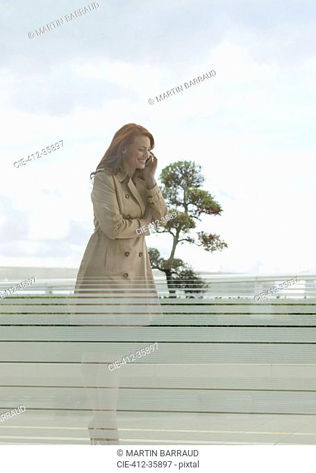 Smiling businesswoman with red hair talking on cell phone on balcony
