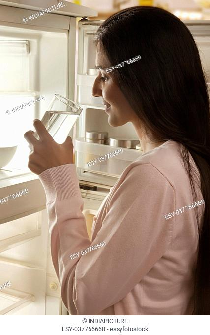 Young woman drinking water in front of open refrigerator