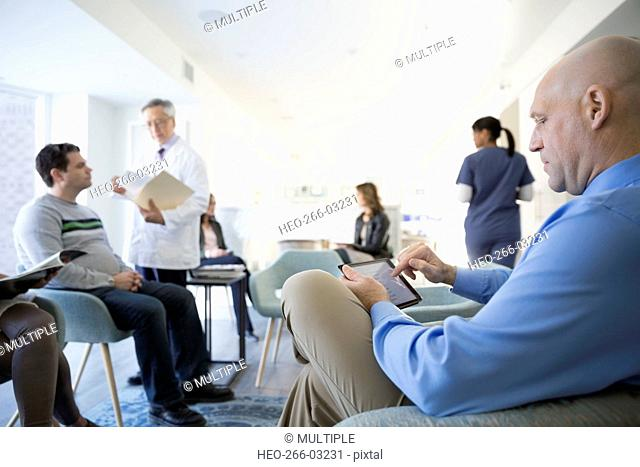 Man using digital tablet waiting in clinic lobby