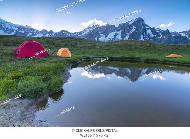 Camping tents in the green meadows surrounded by alpine lake at dusk Mont De La Saxe Courmayeur Aosta Valley Italy Europe