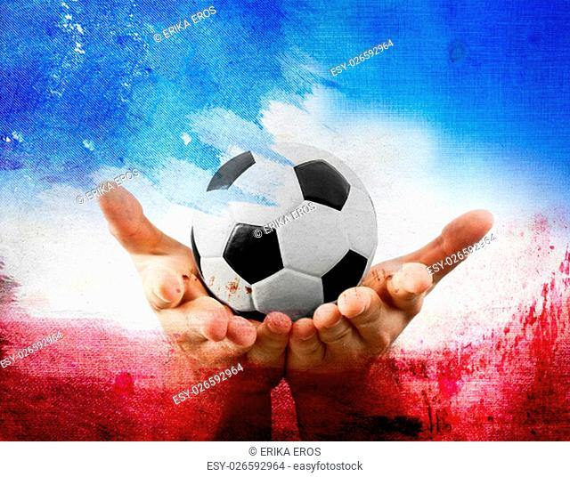 Soccer ball in the hands of a man on red,blue, and white background