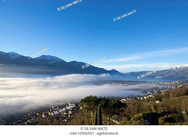 Alpine village under sea of fog over an alpine lake with snow-capped mountain in locarno ticino Switzerland, Europe