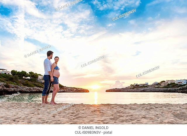 Pregnant woman and man standing together on beach, holding hands, watching sunset