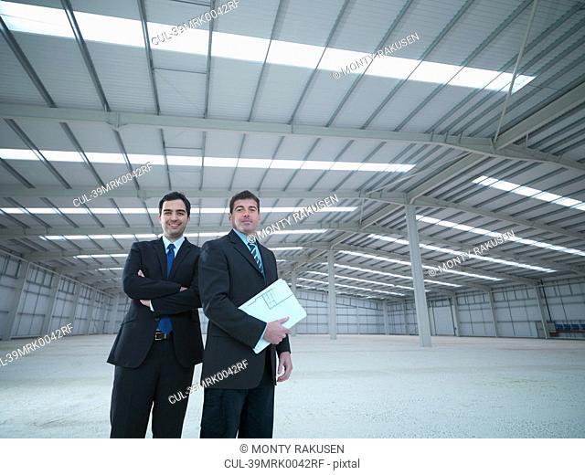 Businessmen standing in empty warehouse