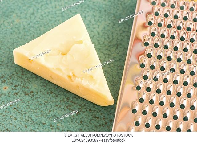 Cheese and stainless steel grater in close-up. Kitchen appliance used for grating in food preparation
