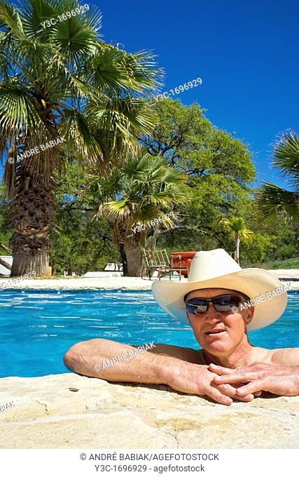 Middle-aged man with cowboy hat and sun glasses refreshing and relaxing in a swimming pool