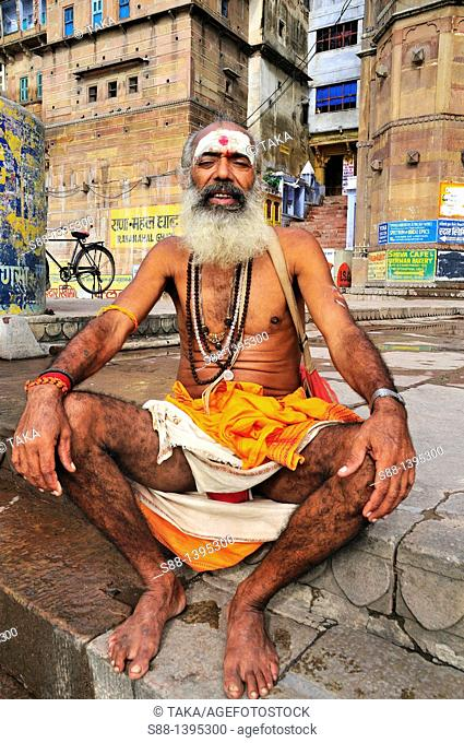 Sadhu sitting at the ghat by the Ganges river