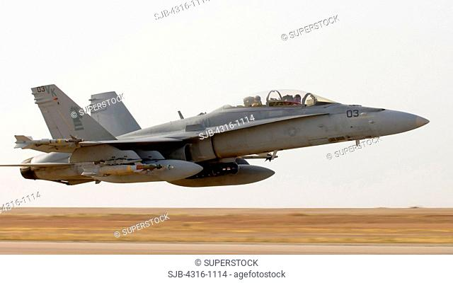 A US Marine Corps F/A-18D Roars Just Feet Above a Runway at Over 300 Knots During an Unrestricted Takeoff from Al Asad Air Base in the Al Anbar Province of Iraq...