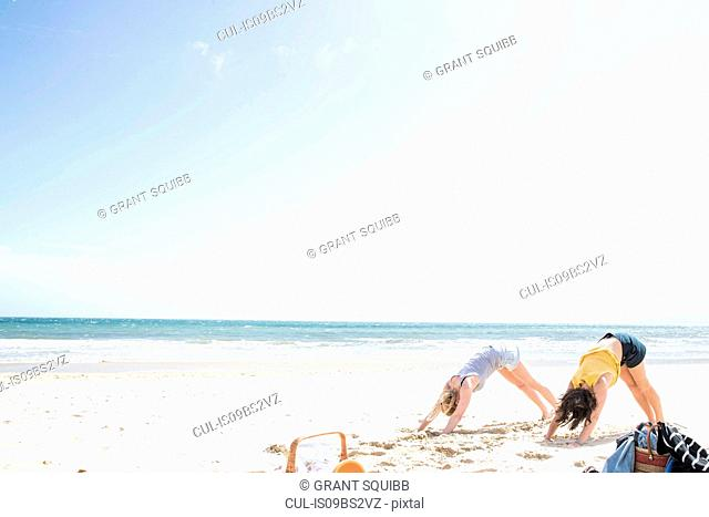 Sisters enjoying yoga on beach