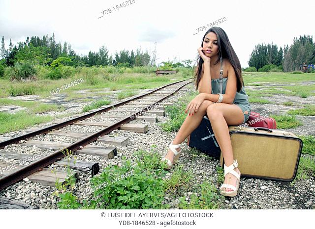 Young woman sitting next to the railroad tracks, Miami, Florida, USA