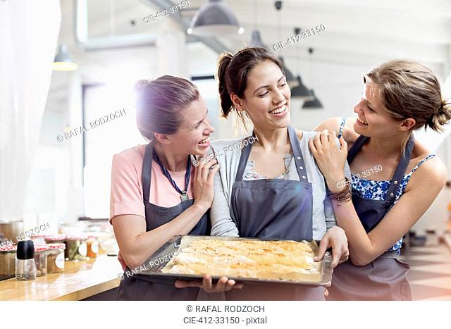 Smiling female friends enjoying cooking class in kitchen