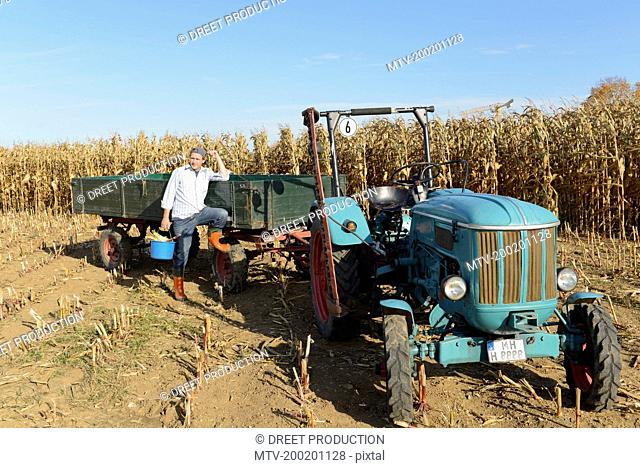 Farmer with tractor on cornfield, Bavaria, Germany