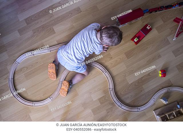 Child boy playing with wooden toy train. Top view. Educational toys