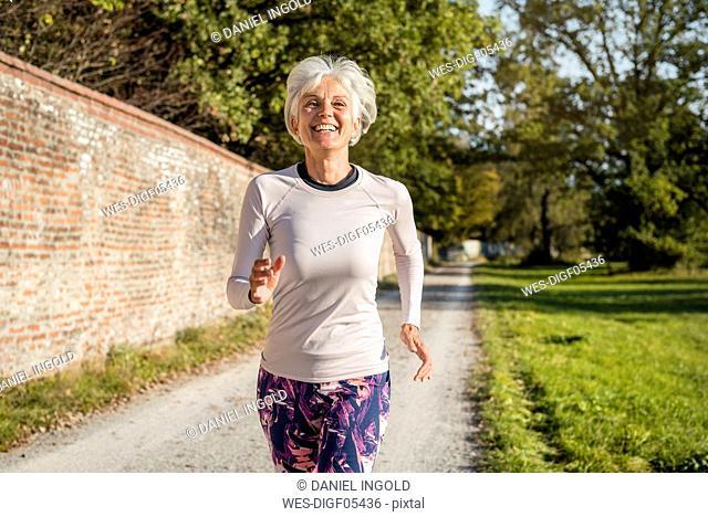 Happy senior woman running along brick wall in a park