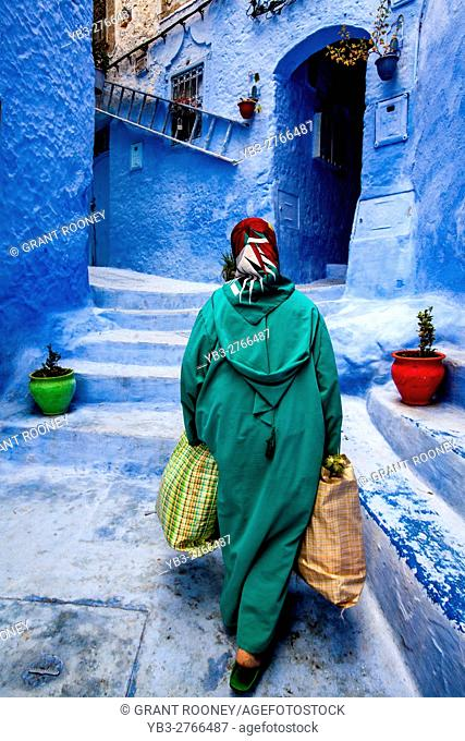 An Elderly Woman Walks Through The Colourful Streets Of The Medina With Heavy Shopping Bags, Chefchaouen, Morocco