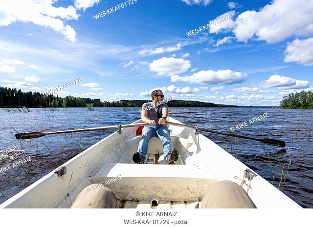 Finland, Man rowing in a boat on a lake