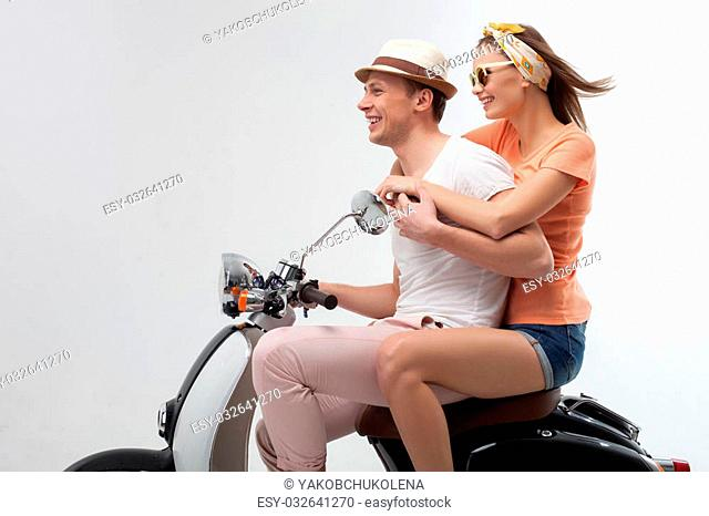 Portrait of cheerful young man and woman traveling by scooter. They are sitting in profile and looking forward with anticipation