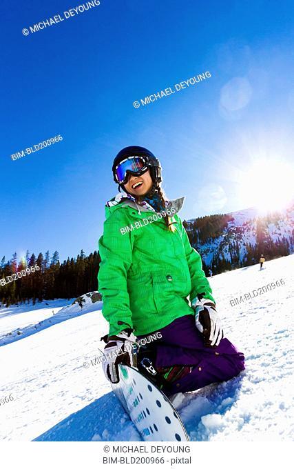 Mixed race teenager snowboarding