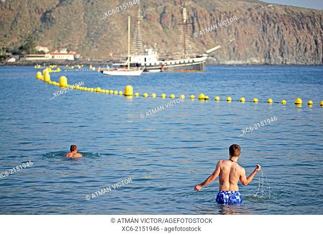 two boys swimming at Los Cristianos beach in Tenerife island spain