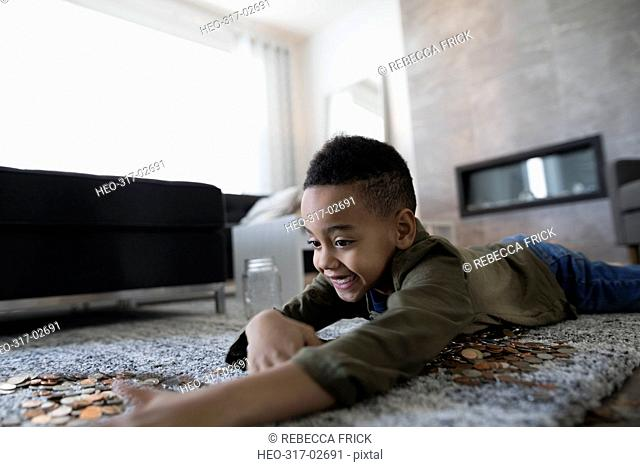 Boy with coins on living room floor