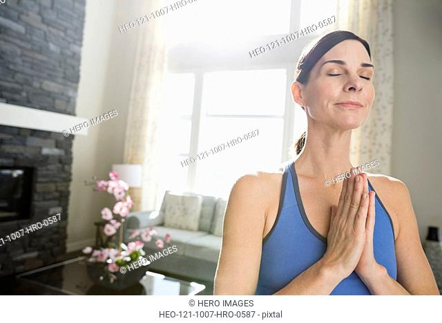 Mature woman with hands clasped meditating at home