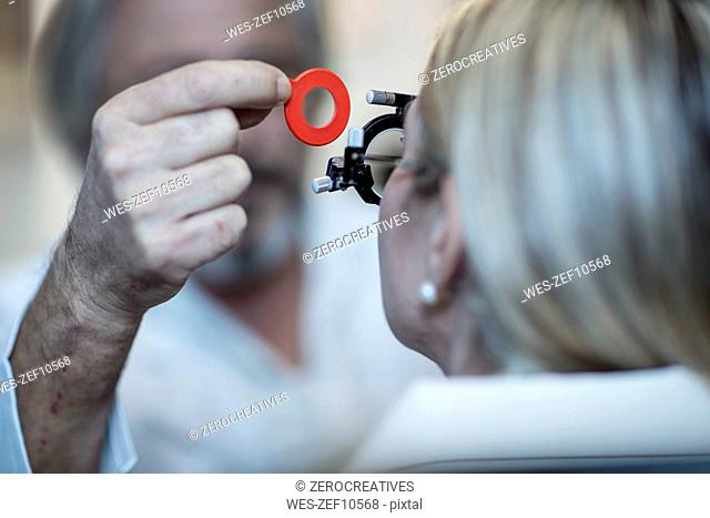 Optometrist adjusting test frame for patient