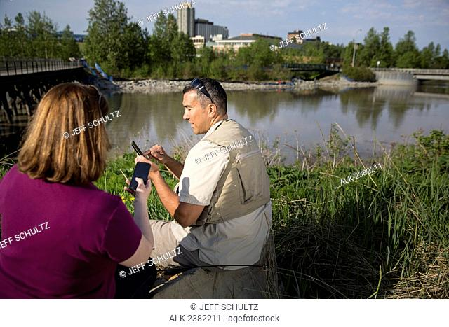 Alaska Native Inupiat man and Caucasian woman texting on smart phone cell phones at Ship Creek Downtown Anchorage, Alaska, Summer